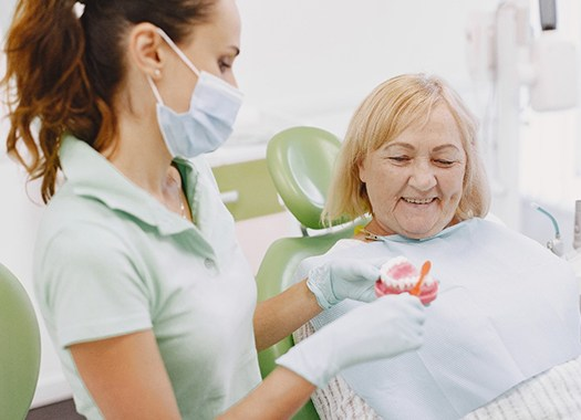 An older woman watches a dentist show her how to take care of All-On-4 dental implants