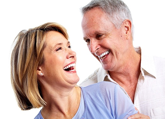 An older couple laughing and smiling because of the new confidence they have in their smiles
