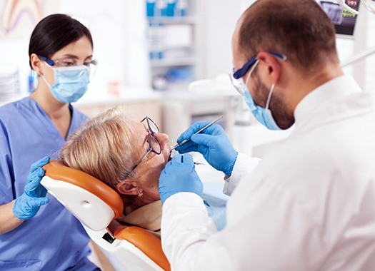 A dentist and hygienist examining a patient's smile during a consultation