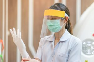 A dental professional wearing PPE your Uptown New Orleans dentist also wears