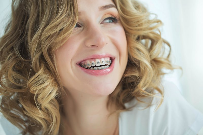 an up-close image of a young woman with blonde hair smiling and showing off her metal braces